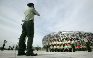 Soldiers tak photographs in front of National Stadium in Beijing