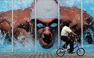 Man cycles past photo of Michael Phelps